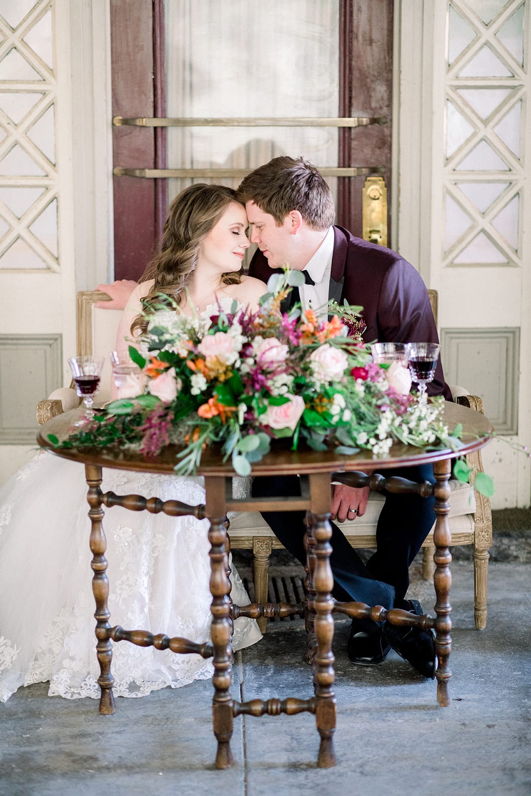 Wedding Couple at a sweetheart table. Table is a vintage gate leg table in an oval shape.