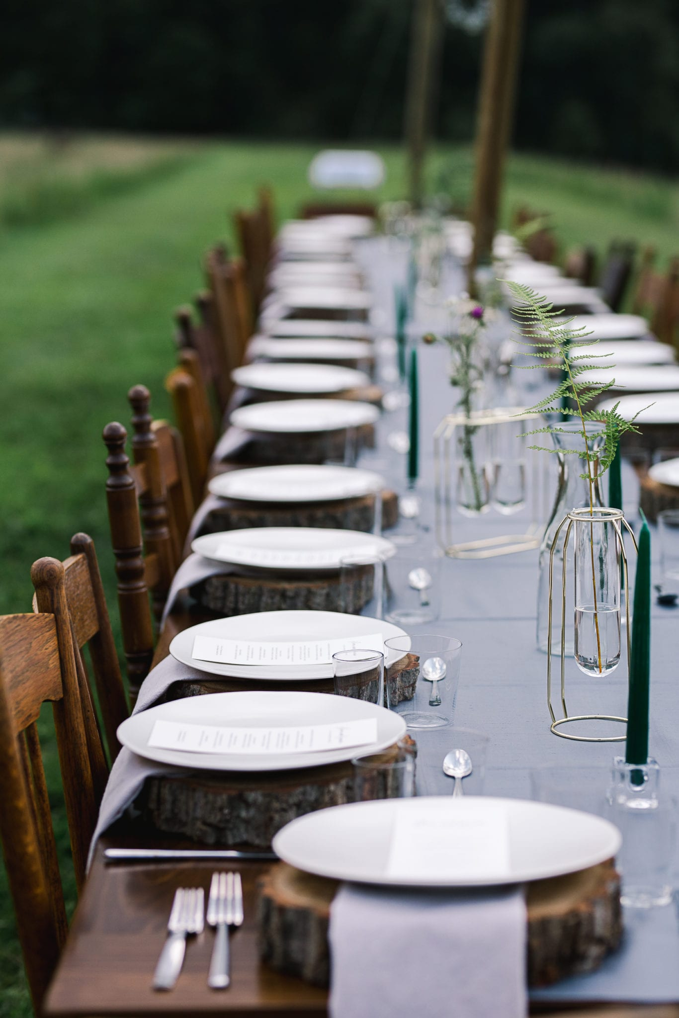 Farm tables with mismatched wooden chairs at outdoor dinner by Sub Rosa Supper Club. Image by Sarah Featherstone Photography.